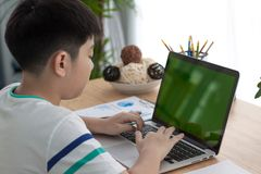 Over the shoulder shot of an Asain boy typing on a computer lapt. Op with a key-green screen. Woman hand typing laptop with green screen Stock Photo