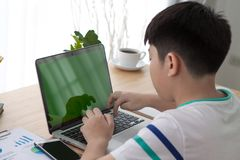 Over the shoulder shot of an Asain boy typing on a computer lapt. Op with a key-green screen. Woman hand typing laptop with green screen Stock Image