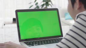 Over the shoulder shot of Asian boy looking at green screen. stock footage
