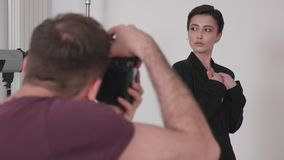 Over the shoulder shot of professional photographer taking pictures of a model. In studio on a white background stock footage