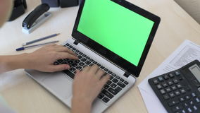 Over the shoulder shot of a woman typing on a laptop with a key-green screen. stock video
