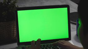 Over the shoulder shot of a young boy using on laptop computer on desk, stock footage