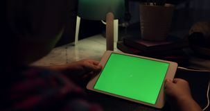 Over the shoulder view of asian boy using tablet computer with headphone, Green screen of technology being used. Chroma Key tablet. Over the shoulder view of stock footage