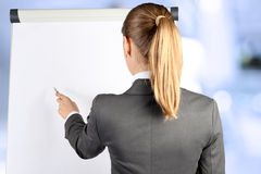 Over the shoulder view of blonde businesswoman pointing on a whi Royalty Free Stock Images