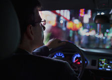 Over the shoulder view of businessman driving at night in the city, illuminated city lights Royalty Free Stock Image
