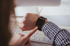 Over the shoulder view of businesswoman using her smart watch. At her desk in office Stock Photo