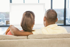 Over shoulder view of casual couple watching tv Stock Image
