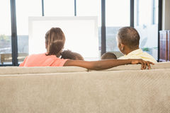 Over shoulder view of casual family watching tv Stock Photos
