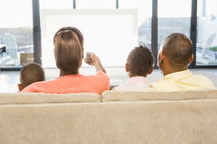 Over shoulder view of casual family watching tv. In living room Stock Photography