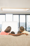 Over shoulder view of casual family watching tv. In living room Stock Images