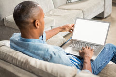 Over shoulder view of casual man using laptop Royalty Free Stock Photos