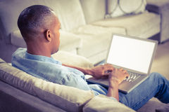 Over shoulder view of casual man using laptop Royalty Free Stock Images