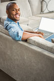 Over shoulder view of casual man using laptop Royalty Free Stock Image
