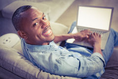 Over shoulder view of casual man using laptop Stock Image