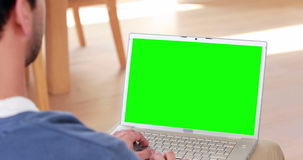 Over shoulder view of casual man using laptop stock footage