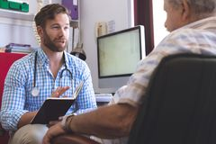 Male doctor prescribing medicament  to senior man in clinic stock photos