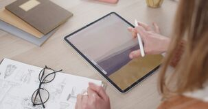 Over shoulder view of female artist drawing lines, zooming and rotating while creating illustration on tablet.Woman