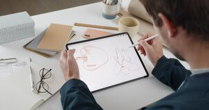 Over shoulder view of fmale artist drawing illustration on tablet while sitting at workplace. Graphic illustrator using