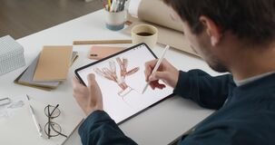 Over shoulder view of fmale artist drawing plant while creating illustration on tablet.Man graphic illustrator using
