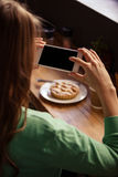 Over the shoulder view of hipster woman taking picture of pastry Stock Image