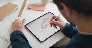 Over shoulder view of male artist drawing bird while creating illustration on note pad. Guy graphic illustrator using