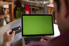 Over shoulder view of man shopping on-line with credit card Royalty Free Stock Photography