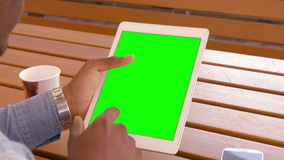 Over shoulder view of man using tablet. Sitting outdoors stock video
