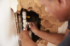 Over shoulder view of middle aged man repairing burst pipe stock image