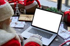 Santa Claus using laptop computer mock up white screen sitting at table.