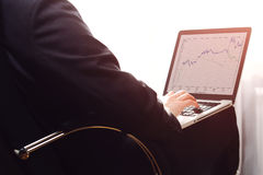 Over the shoulder view of the screen of a businessman analyzing graphs on his laptop. Computer located on knees. Royalty Free Stock Photo