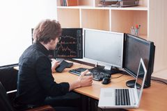 Over the shoulder view of and stock broker trading online while accepting orders by phone. Multiple computer screens ful. Of charts and data analyses in royalty free stock photos