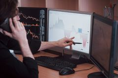 Over the shoulder view of and stock broker trading online while accepting orders by phone. Multiple computer screens ful. Of charts and data analyses in royalty free stock photography