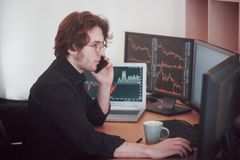Over the shoulder view of and stock broker trading online while accepting orders by phone. Multiple computer screens ful. Of charts and data analyses in royalty free stock image