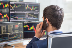 Over the shoulder view of stock broker trading online, talking on mobile phone. Over the shoulder view of and stock broker trading online while accepting orders Stock Photos