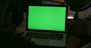 Over the shoulder view of  typing and watching on computer . Green screen of technology being used. Chroma Key laptop stock footage