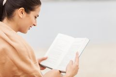 Over shoulder view of woman reading book covered with blanket. Stock Image