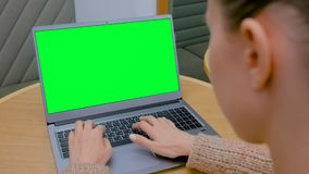 Woman typing on laptop computer keyboard with blank green screen in cafe. Over shoulder view - woman sitting at table and typing on grey laptop computer keyboard stock video