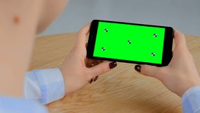 Woman holding black smartphone with blank green screen - chroma key concept. Over shoulder view: woman sitting at wooden table and holding black smartphone with stock footage