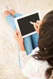 Over shoulder view of woman using tablet. At home Stock Images