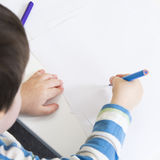 Over shoulder view of a young boy drawing. Over the shoulder view of a young boy drawing with a blue pencil Royalty Free Stock Image