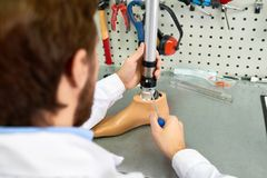 Prosthetist Assembling Artificial Leg. Over the shoulder view of young man assembling artificial foot sitting at table in modern laboratory Royalty Free Stock Images