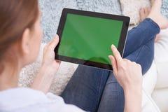 Over The Shoulder Weergeven van Vrouw het Liggen op Sofa Using Green Screen Digital-Tablet thuis stock fotografie