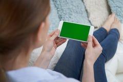Over The Shoulder Weergeven van Vrouw het Liggen op Sofa Using Green Screen Mobile-Telefoon thuis stock foto