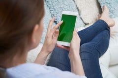Over The Shoulder Weergeven van Vrouw het Liggen op Sofa Using Green Screen Mobile-Telefoon thuis royalty-vrije stock afbeelding