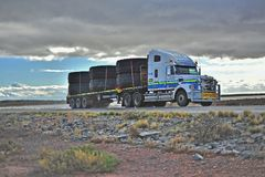 White truck carrying tyres, with storm approaching. royalty free stock image