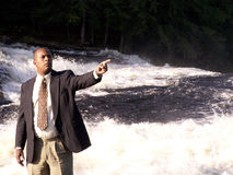 Over there. Business man in a suit standing in front of a rushing river with finger pointing royalty free stock photos