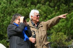 Over There I Think. An elderly married couple sightseeing with binoculars Stock Photos