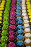 Over three dozen brightly colored cupcakes in vertical rows Stock Photos