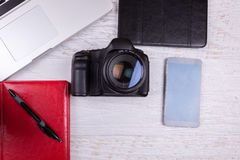 Over top photo of DSLR digital camera and laptop. On wooden background Royalty Free Stock Photos