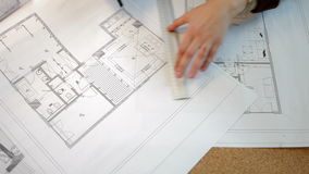 Over top view of architect working on blueprints plan. Blusiness woman with blueprints on the table stock video